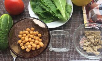 Шаг 1: Приготовьте ингредиенты. Вымойте овощи и листья салата. Нарежьте хлебцы на небольшие кусочки и подсушите. Слейте жидкость из банки с нутом.
