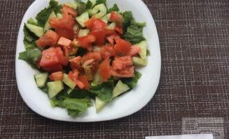Шаг 2: Порвите руками листья салата и выложите на тарелку. Крупно нарежьте помидор и огурец. Выложите поверх листьев салата.