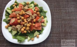 Шаг 3: Далее посыпьте салат нутом и сухариками.
