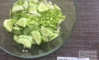 Шаг 3: Нарежьте огурцы ломтиками, зеленый перец полосками. Добавьте в миску к нарезанной капусте.