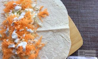 Шаг 6: Выложите на лаваш морковь, капусту и лук, полейте соусом.