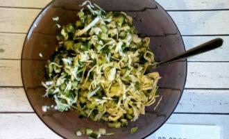 Шаг 4: В глубокой ёмкости смешайте капусту, огурцы, зелёный лук, укроп.