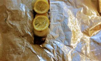 Шаг 4: Посолите и поперчите по вкусу. На рыбку уложите порезанный лук и лимон с обеих сторон. Можно также и внутрь.