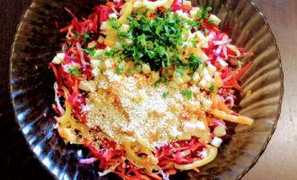 Шаг 7: Мелко порежьте зелень, огурцы и высыпьте в салат. Посолите, поперчите, полейте оливковым маслом и посыпьте кунжутом.