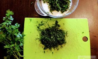 Шаг 4: В тарелку с йогуртом высыпьте петрушку. Укроп мелко порубите и добавьте в соус.