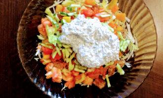 Шаг 8: Куриное филе отварите, порежьте кубиками и выложите в салат. Огурец нарежьте соломкой, высыпьте к остальным ингредиентам и добавьте заправку .