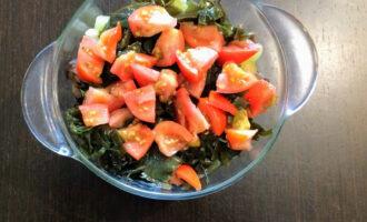 Шаг 6: Помидор помойте, порежьте кубиками и выложите в тарелку с салатом.