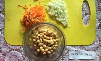 Шаг 1: Подготовьте необходимые ингредиенты. Предварительно, минимум на 8 часов замочите нут в воде. После этого нут промойте под водой, пересыпьте в блендер, добавьте воду 50 мл. и измельчите до однородной массы. Нарежьте лук, и потрите морковь на терке.