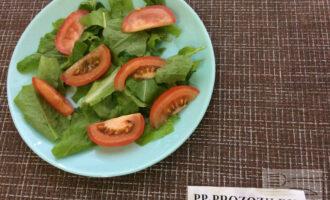 Шаг 2: Порвите салат руками и выложите на тарелку. Нарежьте помидор дольками и выложите на листья салата.