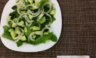 Шаг 2: Мелко нарвите салат руками и выложите на тарелку. Далее выложите нарезанный кубиками огурец и измельченный лук.