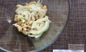 Шаг 2: Высыпьте фасоль в глубокую миску. Добавьте нарезанный полукольцами лук.