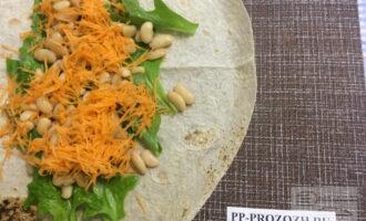 Шаг 3: На листья выложите фасоль, затем натертую морковь.