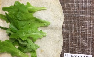 Шаг 4: Выложите листья салата на лаваш. Нарежьте лук полукольцами.