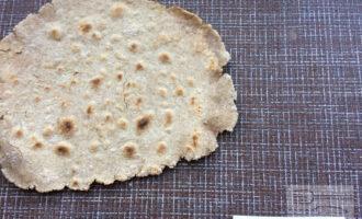 Шаг 3: Раскатайте тесто тонким слоем. Выпеките лаваш на сухой раскаленной сковороде до появления небольших пузырей.