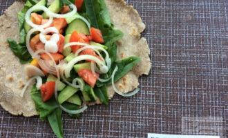 Шаг 4: Нарежьте помидор и огурец. Репчатый лук нарежьте полукольцами. Выложите листья салата на лаваш, затем остальные овощи в произвольном порядке. Слегка посолите и сбрызните оливковым маслом.