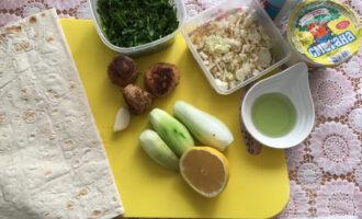 Шаг 4: Подготовьте лаваш, нарежьте огурцы и пекинскую капусту. Для соуса: оливковое масло, сметана, чеснок, зелень, соль. Смешайте все ингредиенты в миске.