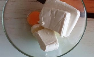 Шаг 2: В глубокую миску выложите творог. Влейте в творог яйцо. Добавьте соль. Тщательно перемешайте.