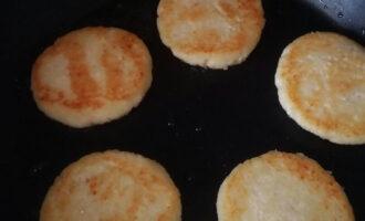 Шаг 6: Через 3-5 минут переверните сырники и обжарьте с другой стороны до состояния готовности.