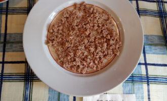 Шаг 2: На тарелку выложите первый слой  из тунца.