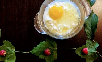Шаг 2: В глубокую тарелку высыпьте творог и вбейте яйцо.
