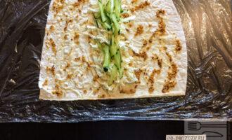 Шаг 4: Огурец помойте, порежьте соломкой и разложите на пекинскую капусту.