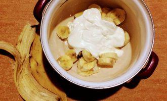 Шаг 3: Банан очистите от кожуры, порежьте и высыпьте в глубокую кастрюлю. Добавьте сметану.