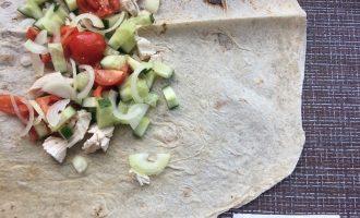 Шаг 3: Нарежьте овощи и куриное филе небольшими ломтиками, лук нарежьте полукольцами. Выложите слоями на лаваш. Полейте соусом, сверху положите листья салата.
