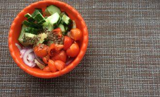 Шаг 4: Огурец и помидоры нарежьте на небольшие ломтики. Лук нарежьте полукольцами. Заправьте салат заправкой и перемешайте.