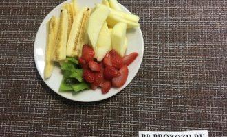 Шаг 2: Нарежьте яблоко, киви и банан на полоски. Клубнику — на дольки. Выдавите лимонный сок. Сбрызните фрукты лимонным соком.