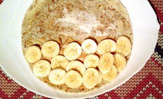 Шаг 5: Одну половину блина смажьте арахисовой пастой. Сверху выложите порезанный банан.