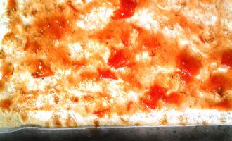 Шаг 2: От лаваша отрежьте один квадрат и смажьте томатным соусом. Это будет основа Вашей пиццы. Если хотите сделать ее более мягкой, то возьмите два таких квадрата из лаваша, промажьте соусом и посыпьте тертым сыром.