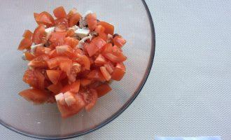 Шаг 4: Помидор нарежьте на небольшие ломтики. Добавьте в миску. Посолите и сбрызните оливковым маслом. Перемешайте.