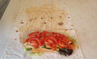 Шаг 4: Лист лаваша смажьте смесью майонеза и соевого соуса. Выложите на лаваш листья салата, рыбу, перец, огурец, помидор.  Сверните лаваш в форме продолговатого конверта, загибая боковые стороны внутрь.