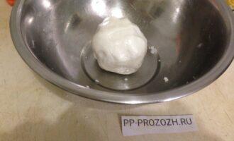 Шаг 2: В миску вылейте приготовленную воду, добавьте соль и размешайте. Замесите тесто, постепенно добавляя муку и оливковое масло. Если тесто получается очень крутое, добавьте немного воды.  Придайте тесту форму шара и оставьте на 15 минут, накрыв полотенцем.