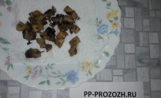 Шаг 4: При помощи острого ножа аккуратно отделите ножки у грибов от шляпок. Ножки нарежьте и слегка обжарьте на кокосовом масле (жарьте не больше одной минуты). Положите ножки на салфетку - уберите излишки масла.