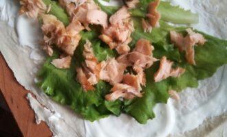 Шаг 3: Положите листья салата сверху. Лосось разделите на кусочки и уложите на салат.