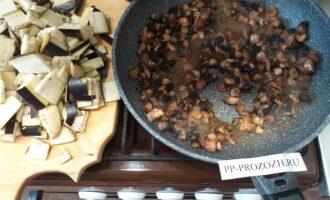 Шаг 3: Вначале, на разогретую сковороду( с антипригарным слоем) поместите грибы, потушите их 3-5 мин. Добавьте баклажаны и продолжайте тушить 7-10 мин.