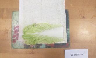 Шаг 3: Положите перед собой лист лаваша узкой стороной к себе. На ближний к вам край лаваша положите лист пекинской капусты.