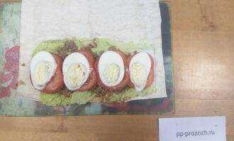 Шаг 7: Яйцо сварите вкрутую. Затем порежьте по длине и выложите сверху на помидоры.