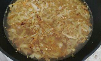Шаг 9: Добавьте булгур к овощам. Залейте водой чтобы капусту скрывало. И отправьте тушиться до исчезновения воды. За 5 минут до готовности добавьте соевый соус, и вновь перемешайте.