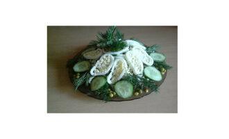 Шаг 7: Выложите готовый салат горкой на блюдо, украсьте колечками кальмаров, ломтиками огурцов, желтками яиц и зеленью.