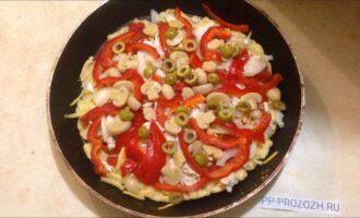 Шаг 5: На основу выложите помидоры, присолите, если нужно. Сверху посыпьте сыром. На сыр выложите остальную начинку.  Отправьте пиццу в духовку на 10-15 минут.