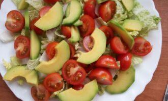 Шаг 4: Авокадо почистите, порежьте полукольцами и выложите на помидоры.
