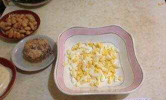 Шаг 2: Яйца отварите и нарежьте кубиками. Выложите в салатницу.