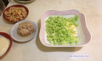 Шаг 3: Огурец почистите, нарежьте кубиками и добавьте к яйцам.
