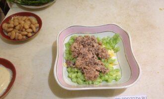 Шаг 4: Консервы без жидкости разомните вилкой и добавьте в салатницу.