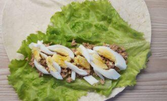 Шаг 4: На тунца выложите предварительно сваренное куриное яйцо.