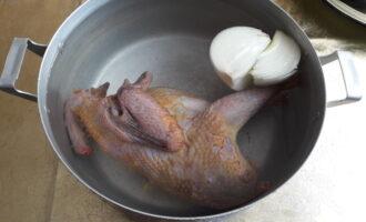 Шаг 2: Положите цесарку в холодную воду, туда же добавьте половину луковицы. Поставьте на плиту и отварите до готовности.