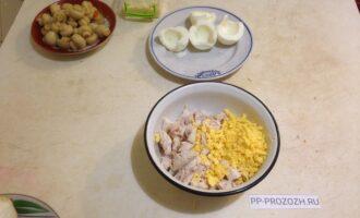Шаг 2: Филе курицы порежьте, выложите в подходящую посуду.  Отделите желтки от белков, потрите желтки на терке и добавьте к курице.  Добавьте пару ложек майонеза и перемешайте. Разделите на две равные части.