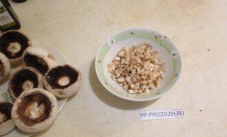 Шаг 2: Отделите ножки грибов и мелко порежьте.